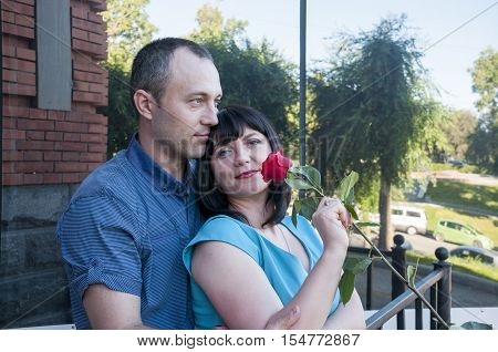 Man and woman standing next to a rose