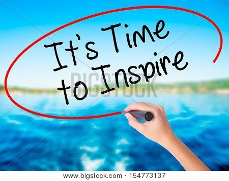 Woman Hand Writing It's Time To Inspire With A Marker Over Transparent Board