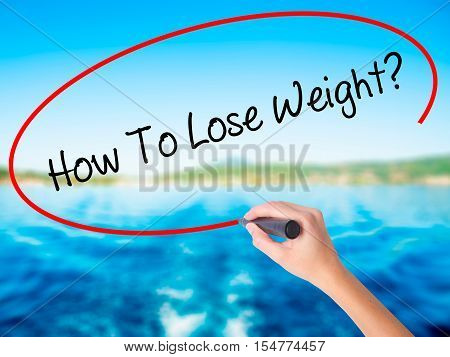 Woman Hand Writing How To Lose Weight? With A Marker Over Transparent Board