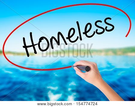 Woman Hand Writing Homeless With A Marker Over Transparent Board.