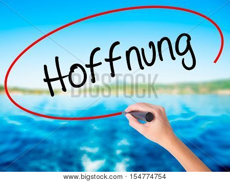 Woman Hand Writing Hoffnung (hope In German)   With A Marker Over Transparent Board