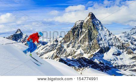 Skier skiing downhill in high mountains in fresh powder snow. Snow mountain range with Matterhorn in background. Zermatt Alps region Switzerland.
