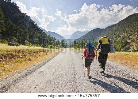 two hikers with poles and backpacks walking in Turkey mountains, Aladaglar, against the sun