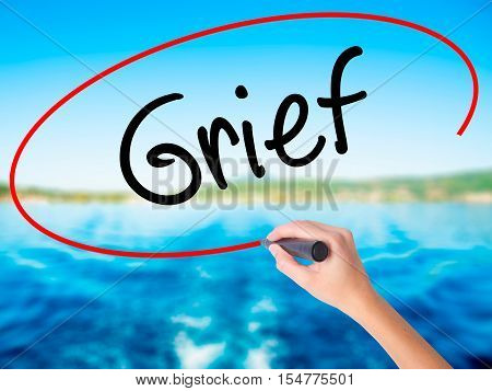 Woman Hand Writing Grief With A Marker Over Transparent Board