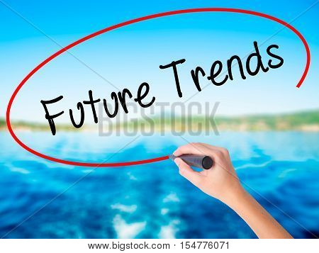 Woman Hand Writing Future Trends With A Marker Over Transparent Board