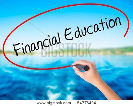 Woman Hand Writing  Financial Education With A Marker Over Transparent Board
