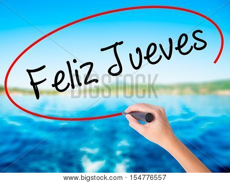 Woman Hand Writing Feliz Jueves (happy Thursday In Spanish) With A Marker Over Transparent Board.