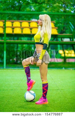 MOSCOW - JUL 16, 2015: beautiful blonde woman (with model release) in top with ball on soccer field, looking throw