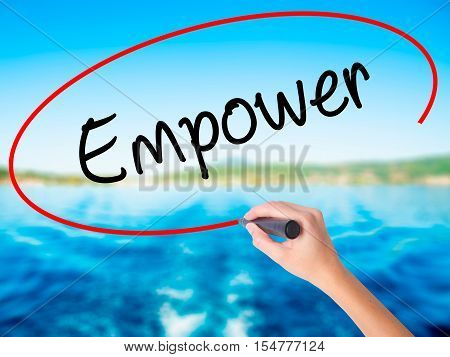 Woman Hand Writing Empower With A Marker Over Transparent Board