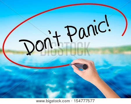 Woman Hand Writing Don't Panic! With A Marker Over Transparent Board