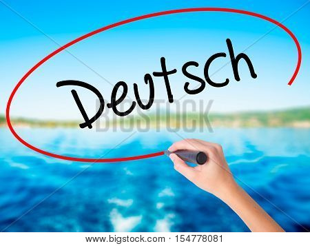 Woman Hand Writing Deutsh (german In German) With A Marker Over Transparent Board