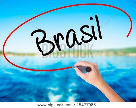 Woman Hand Writing Brasil ( Brazil  In Portuguese) With A Marker Over Transparent Board