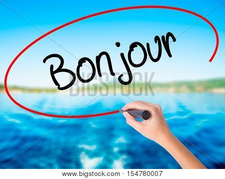 Woman Hand Writing Bonjour  (good Morning In French) With A Marker Over Transparent Board
