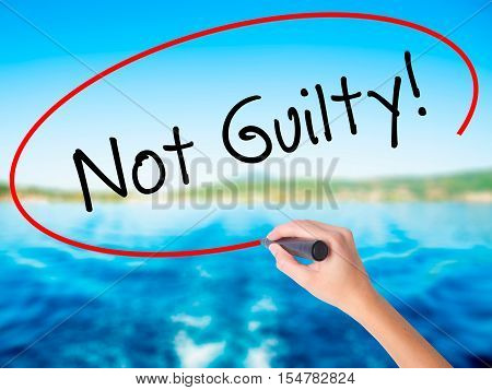 Woman Hand Writing Not Guilty With A Marker Over Transparent Board