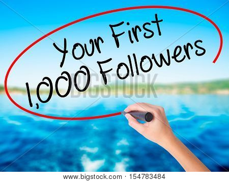 Woman Hand Writing Your First 1,000 Followers  With A Marker Over Transparent Board