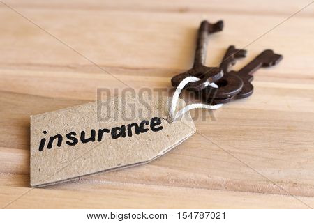 The concept of home insurance - the old key with the inscription on the tag on wooden background.