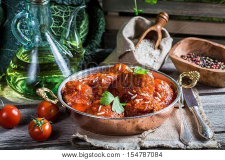Freshly served meatballs in tomato sauce on old wooden table