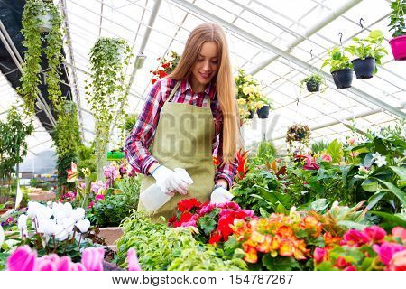 Girl standing in the greenhouse surrounded by colorful plants and sprinkling flowers with airbrush