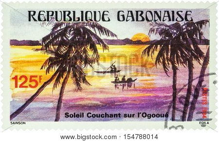 MOSCOW RUSSIA - AUGUST 05 2016: A stamp printed in Gabon shows Evening landscape and canoeing on the tropical Ogooue river series