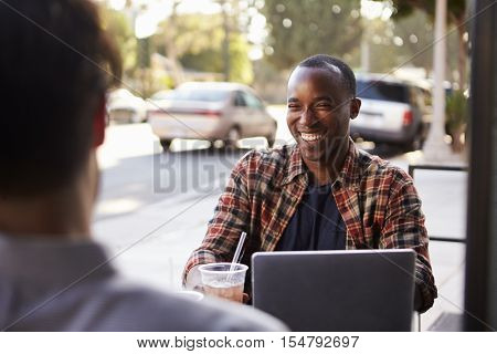 Two male friends with cold drinks and laptop outside cafe