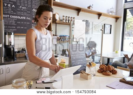 Woman working on the till at a coffee shop, wide angle