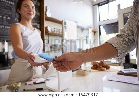 Customer making contactless card payment at a coffee shop
