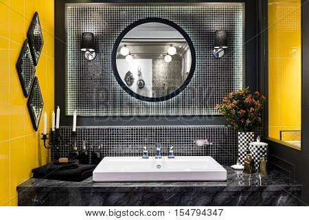 Interior of bathroom with washbasin faucet and black towel in hotel. Modern design of bathroom.
