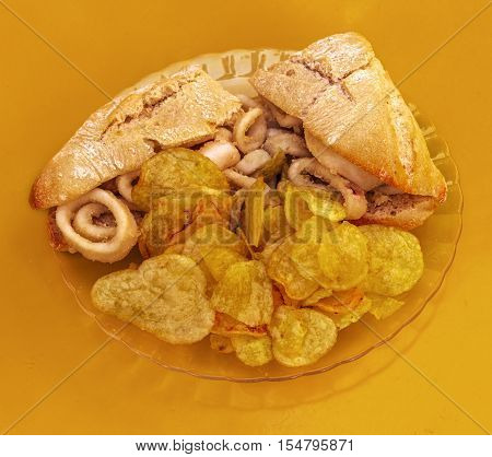 A photo of a squid sandwich, traditional Madrid snack, shot from above on a vibrant yellow background, with copyspace