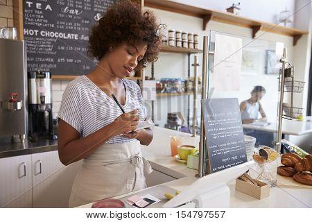 Waitress writing down an order at a coffee shop, close up