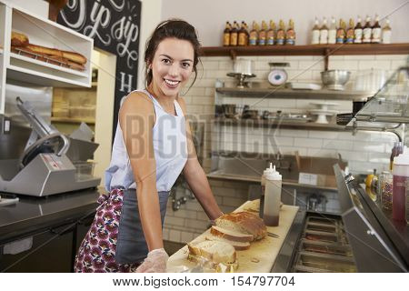 Female business owner of a sandwich bar at work, side view