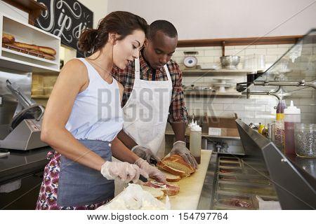 Couple preparing sandwiches at a sandwich bar counter