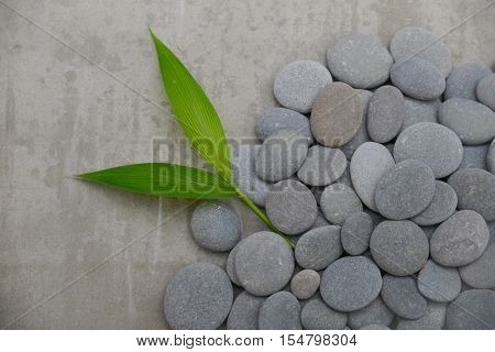 pile of stones with bamboo leaf-gray background