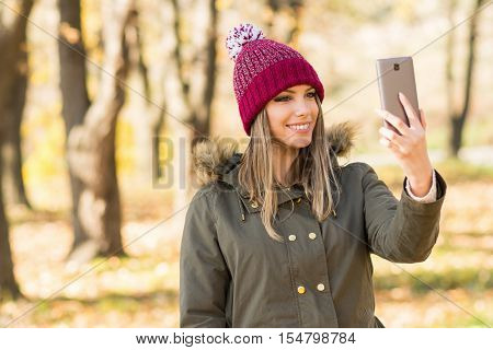 Young happy Caucasian woman taking a selfie on smart phone in park in autumn. Millennial teenage girl in olive green jacket and knitted beanie hat photographing herself on cellphone.