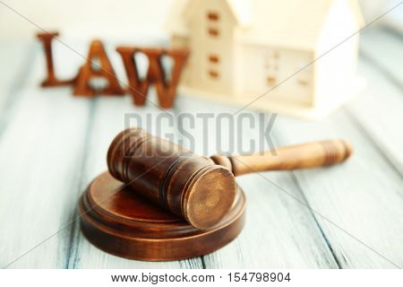 Gavel and miniature house on wooden background