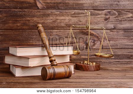 Gavel with books and scales on wooden wall background