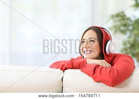Dreamer teen girl listening music with headphones on a couch in the living room at home and looking above with copy space
