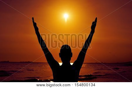 the silhouette of a young man with his arms in the air in front of the sea and the sun in backlight