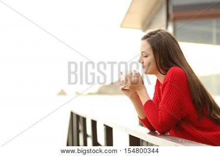 Portrait of a relaxed pensive woman wearing a red sweater holding a cup of coffee in a house or hotel in the beach