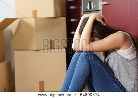 Sad evicted woman worried moving house sitting on the floor in the kitchen