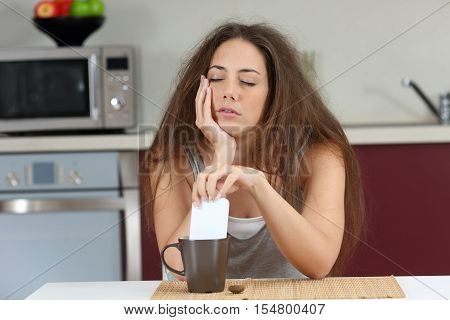 Sleepy tired girl with a bad wake up stirring coffee with the phone sitting in the kitchen at home