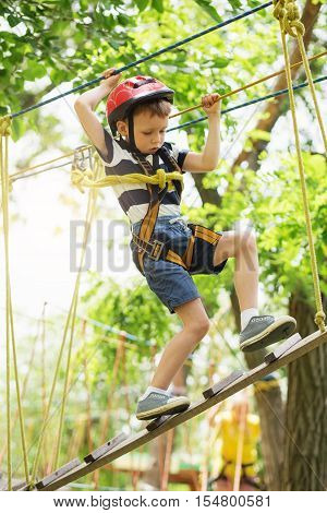 Kids Climbing In Adventure Park. Boy Enjoys Climbing In The Ropes Course Adventure.