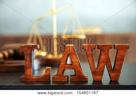Word LAW made of wooden letters on table and blurred background