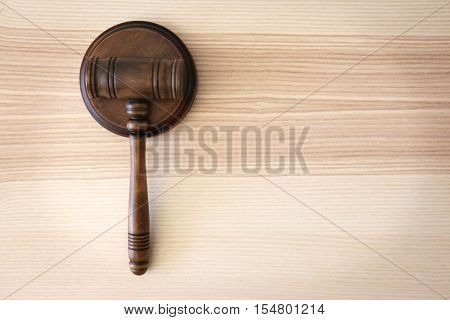 Judges gavel on wooden table, top view