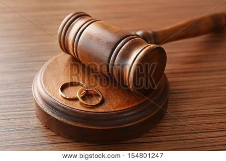 Golden wedding rings with judge gavel, closeup