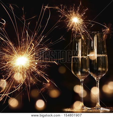 New Year motif at night with fireworks bokeh and two champagne glasses