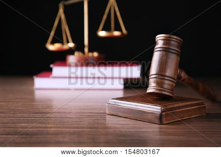 Judges gavel with scales and books on wooden table and black background