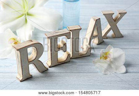 Word RELAX made of letters with flowers on wooden background