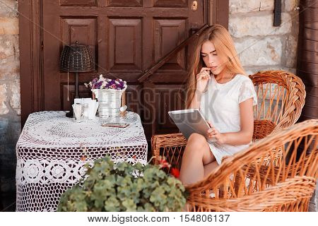 Technology and coziness. Beautiful young woman using tablet computer while sitting on armchair at home.