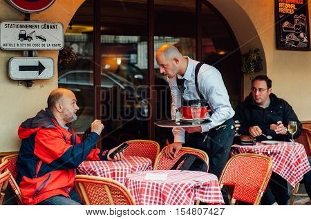 PARIS FRANCE - NOVEMBER 4 2015: Man talks with waiter at street cafe on November 4 2015 in Montmartre. Waiter holds tray with utensils
