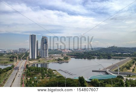 Landscape view of Putrajaya Pullman lakeside and dam from high angle view with white and blue skies during daytime.